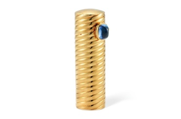 Cartier lipstick holder, circa 1950 Of reeded cylindrical form, the lid cushion shaped cabochon sapphire thumbpiece opening to reveal the lipstick, the base with engraved initialsA.F., French mark, Signed Cartier Paris and numbered indistinctly O1427 £2,000 - £3,000